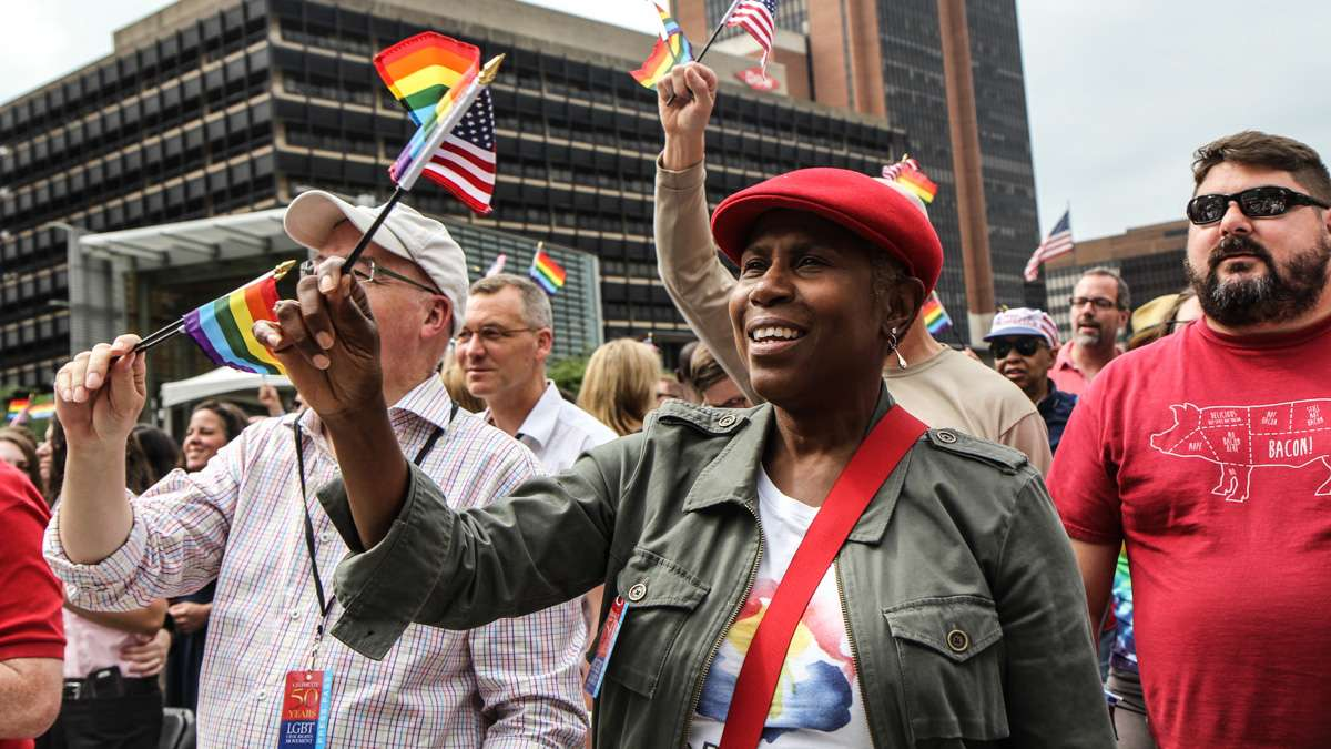 Kati 'Jazzy' Gray-Sadler waves flags during Philadelphia's 4th of July celebration of the 50th anniversary of the LGBT civil rights movement. (Kimberly Paynter/WHYY)