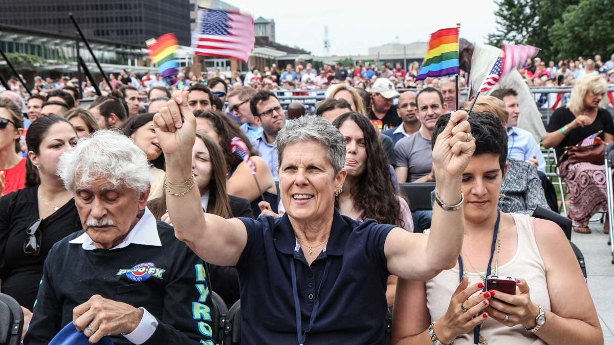 Fay Stevenson waves flags at Philadelphia's 4th of July celebration of the 50th anniversary of the LGBT civil rights movement. (Kimberly Paynter/WHYY)