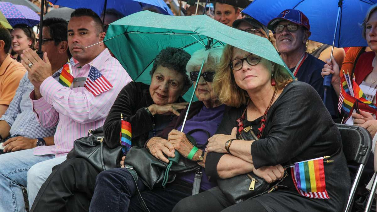 Lillian Faderman, Phyllis Irwin and Kathy hall share an umbrella at Philadelphia's 4th of July celebration of the 50th anniversary of the LGBT civil rights movement. (Kimberly Paynter/WHYY)