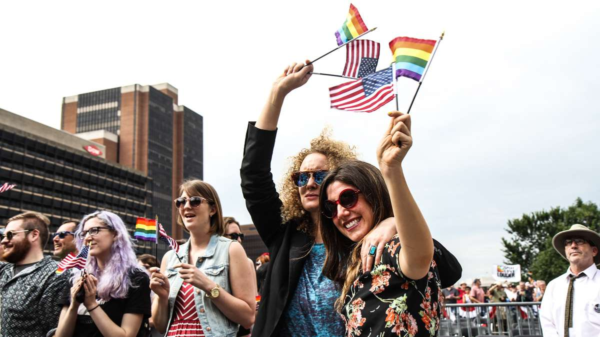 Suanne Podzemny and Dassy Maisel wave flags during Philadelphia's 4th of July celebration of the 50th anniversary of the LGBT civil rights movement. (Kimberly Paynter/WHYY)