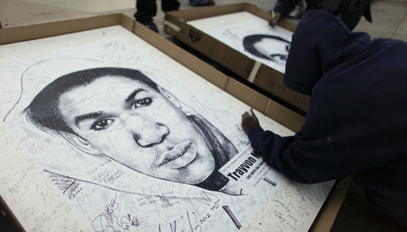 In this March 2012 photo, a supporter of Trayvon Martin signs his name to a poster during a vigil. (Joseph Kaczmarek/AP Photo, file)