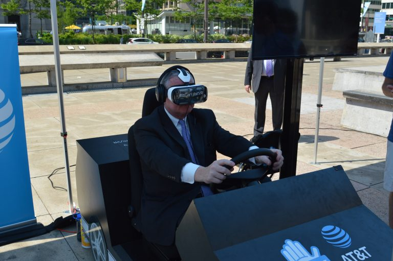 Mayor Jim Kenney tries out a virtual car for a  demonstration of distracted driving. (Tom MacDonald/ WHYY)