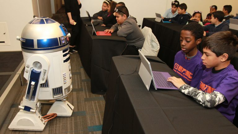 R2-D2 joins New York City students at an Hour of Code pep rally hosted by Code.org, Microsoft and Google at Nasdaq MarketSite in 2015. Students were inspired to try coding with Minecraft and Star Wars themed tutorials. (Donald Traill/ AP Images for Microsoft)
