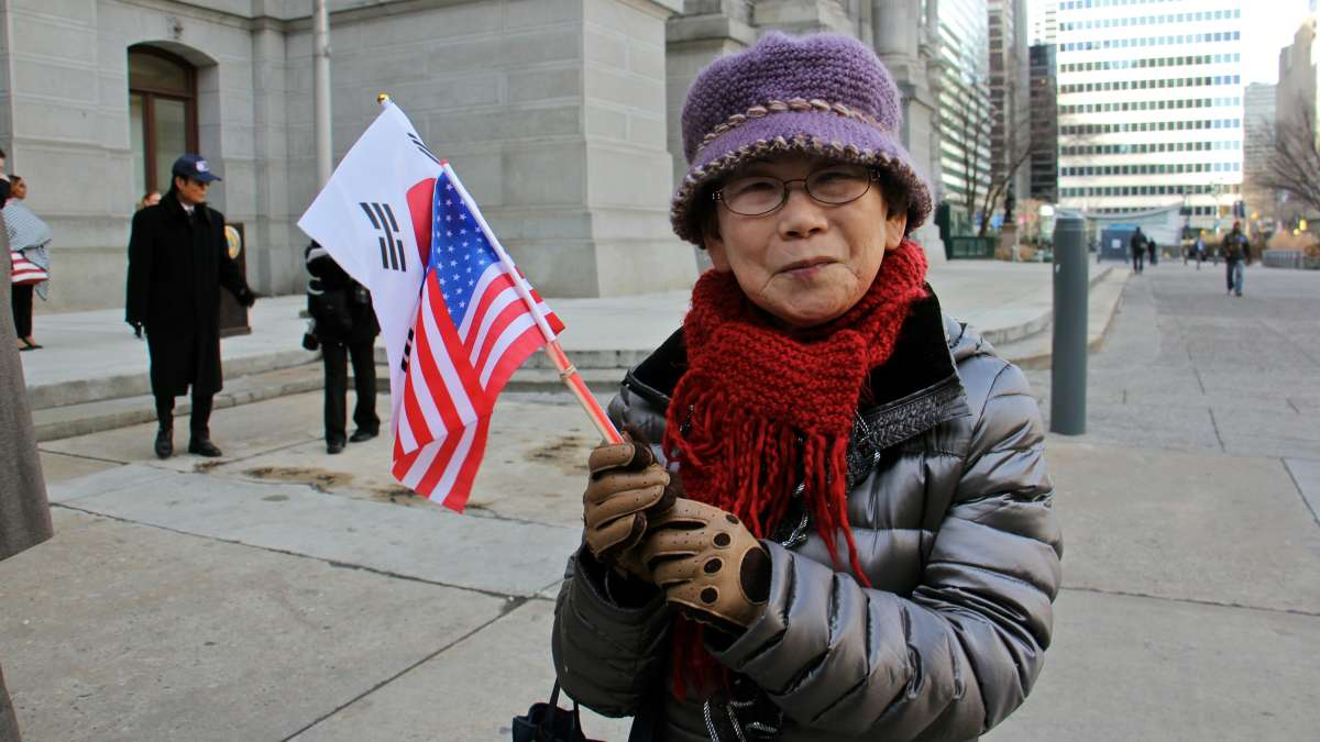 Joo Hwan Yi of Philadelphia waves the flags of the United Statesa and the Republic of Korea