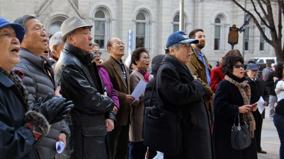 A small crowd gathered outside City Hall for Korean American Day joins in singing ''The Star Spangled Banner'' and the Republic of Korea National Anthem