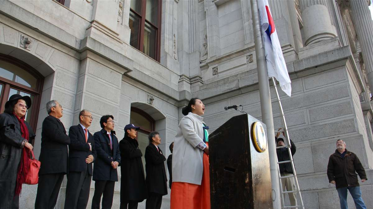 Ji Hyun Choe of the Society of Young Korean Americans sings the Republic of Korea National Anthem as the Korean flag is raised outside City Hall in recognition of Korean American Day.