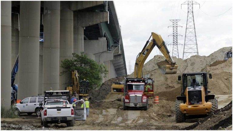 Crews remove dirt from the base of columns supporting  I-495 in 2014. (AP Photo/Patrick Semansky)