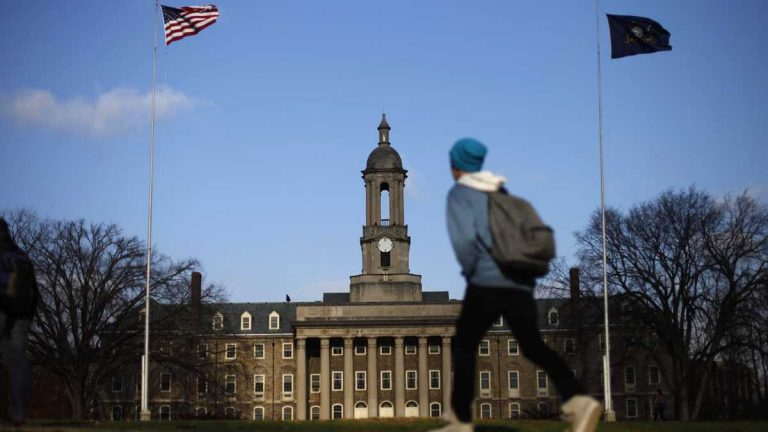 A student walks in front of the Old Main building on the Penn State campus. (Matt Rourke/AP Photo, file)