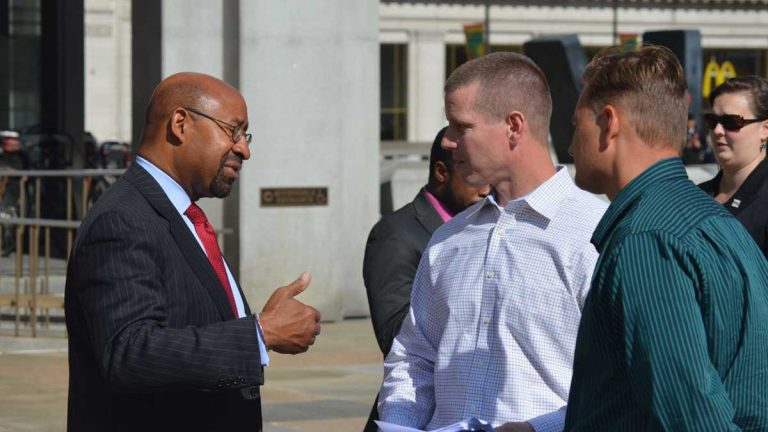 Mayor Michael Nutter, (left), speaks with Joe Schulle, head of the Philadelphia firefighters union Local 22, outside the Municipal Services Building in this file photo. (Tom MacDonald/WHYY)