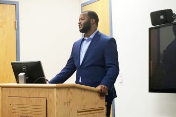 Penn State junior Brian Davis addresses a small group of people who have