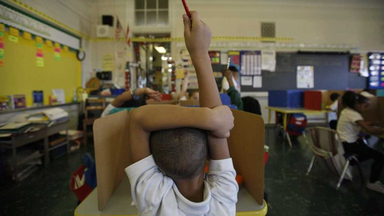 A student raises his hand at Isaac Sheppard School in Philadelphia. (Photo by Jessica Kourkounis)