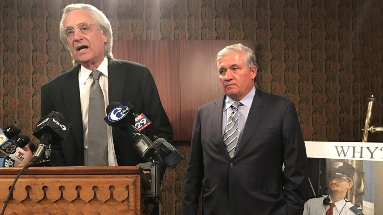Representing crash victims, attorneys Thomas Kline (left) and Robert Mongeluzzi address reporters at a news conference on Thursday next to a photo of Amtrak 188 engineer Brandon Bostian. Pennsylvania Attorney General Josh Shapiro has charged Bostian causing a catastrophe, eight counts of involuntary manslaughter and other crimes. (Bobby Allyn/WHYY)