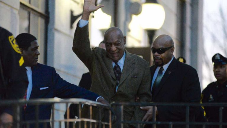 Bill Cosby smiles and waves while leaving the courthouse February 4