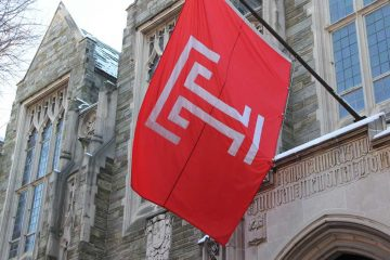 Cherry and white Temple University flag hangs outside of old stone buildings