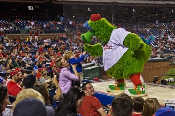 A young fan high-five's the Phillie Phanatic (Kimberly Paynter/WHYY)