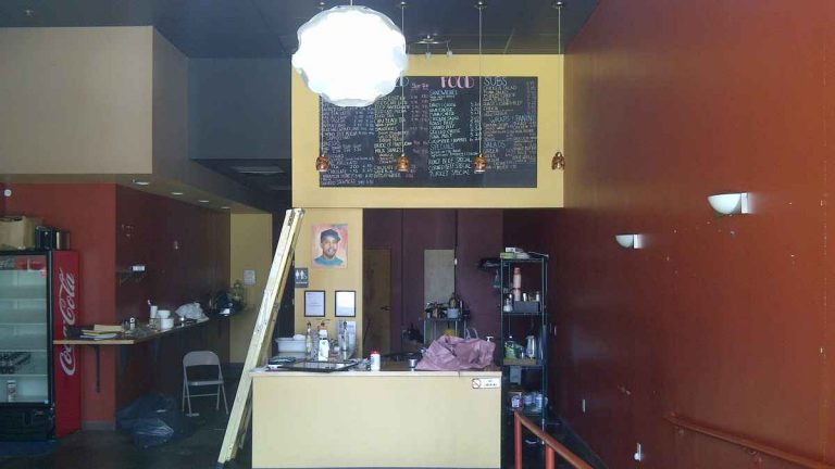 The view inside the now-shuttered Wired Beans Cafe at Germantown's Chelten Plaza. A painting of owner Robert Wheeler sits to the right of the ladder. (Brian Hickey/WHYY)