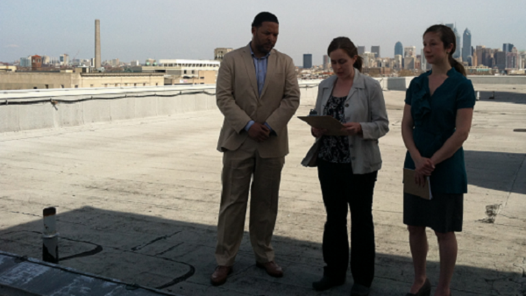 In April, South Philadelphia HS Principal Otis Hackney, Kim Massare of the Lower Moyamensing Civic Assn. and Lauren Mandel from Roofmeadow landscape architecture firm stood on what could become a rooftop farm. (Emma Jacobs/WHYY)
