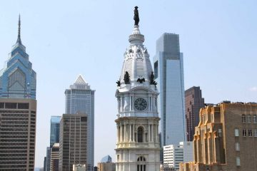 A statue of William Penn atop Philadelphia's City Hall can be seen in the forefront of a portion of the city's skyline (WHYY, file)