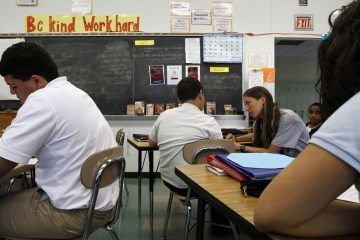 In this file image, teacher Laura Kangay, center, helps a student with his reading at Lincoln Middle School in Lancaster, Pa. The ACLU of Pennsylvania is filing a lawsuit claiming the Lancaster public school district is turning away student refugees in their late teens. (AP File Photo/Alex Brandon)