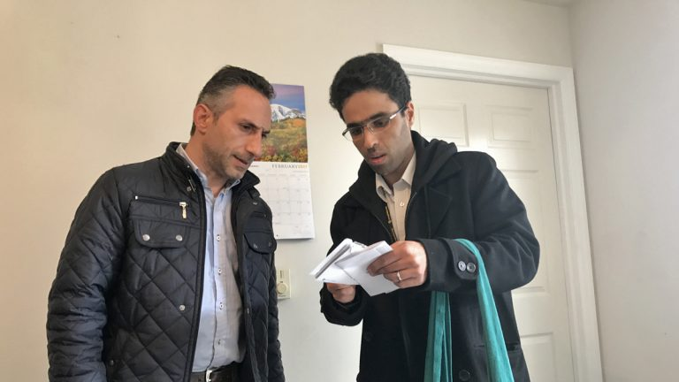 Imad Ghajar (left), a Syrian refugee, reviews paperwork with Amer Alfayadh, caseworker for Church World Service's, in Lancaster, Pennsylvania. (Emily Previti/WITF)
