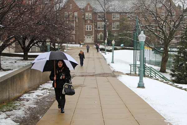 A woman with an umbrella walks through the snow-covered La Salle campus.