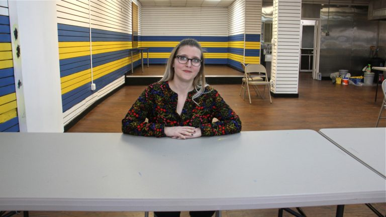Laure Biron, director of the  Porch Light Program for Philadelphia Mural Arts, sits in the program's newly burnished storefront on Kensington Avenue. (Emma Lee/WHYY)