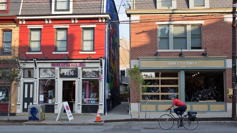 A cyclists rides past restaurants and boutique shops on Butler Street in the Lawrenceville neighborhood of Pittsburgh, Pa. (Lindsay Lazarski/WHYY)