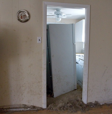 <p><p>Mounds of sand and the refrigerator block the entrance way into the kitchen. (Lindsay Lazarski/WHYY)</p></p>