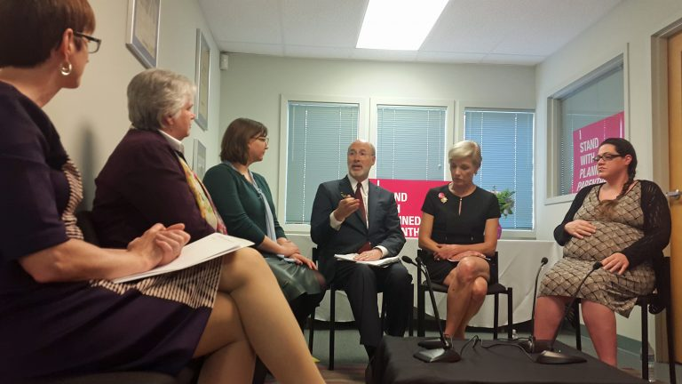 Governor Tom Wolf speaks at the Planned Parenthood in Warminster. He is seated next to PP President Cecile Richards. (Laura Benshoff/WHYY)