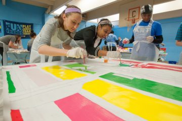 Amanda DeSenna (left) and Marielle Fortune paint one of the canvas squares that will make up Shira Walinsky's new mural, ''Migrating Home.'' (Jonathan Wilson for NewsWorks)