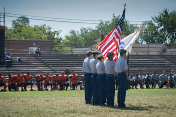 Junior ROTC members at Woodrow Wilson High School hold the American flag during the national anthem
