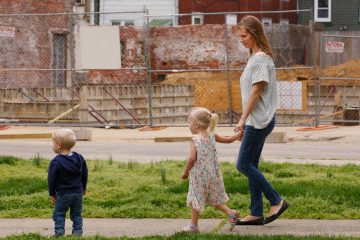 Jana Curtis and two of her children walk past one of many construction sites in their river ward neighborhood. Three-year-old Nolyn Pace, center, was poisoned by lead in the soil in their backyard. (Jessica Griffin/Philadelphia Media Network)