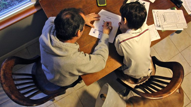 José helps his 7-year-old son with homework at their home in central New Jersey. (Emma Lee/WHYY)