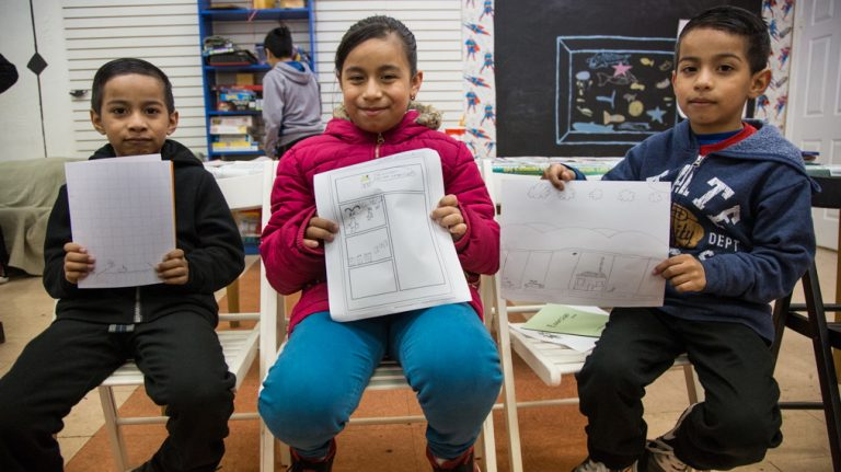 Siblings, Rogyer, 7, Jeidi, 8, and Romny, 7, show off their comics. Almost all of the comics the students have made illustrate the fear they have of ICE and the possible separation of their families. Mighty Writers El Futuro in South Philadelphia hosted a 10-class comic book workshop created by Nora Litz to help give their students a new outlet to talk about their fears after the 2016 elections. (Emily Cohen for NewsWorks)