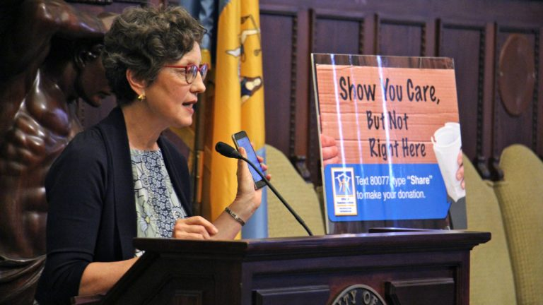Liz Hersh, director of the Office of Homeless Services, urges Philadelphians to use their phone to the Mayor's Fund to End Homelessness rather than hand cash to panhandlers. (Emma Lee/WHYY)