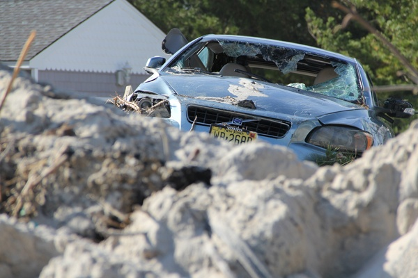 <p><p>A storm-battered car sits atop a pile of sand in a front yard on Bay Avenue in Holgate, N.J., the area of Long Beach Island hardest hit by Sandy. (Emma Lee/for NewsWorks)</p></p>