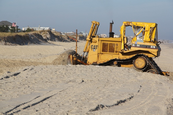 <p>A bulldozer on Long Beach Island moves sand to restore the dunes that were swept away by Hurricane Sandy. (Emma Lee/for NewsWorks)</p>