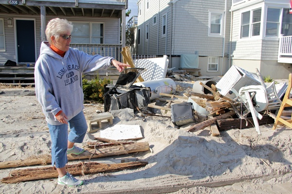 <p><p>Debbie Gutzler sorts through the debris deposited in the front yard of her home on Atlantic Avenue in Beach Haven, N.J. She suspects that much of it came from her neighbor's beach-front home. (Emma Lee/for NewsWorks)</p></p>