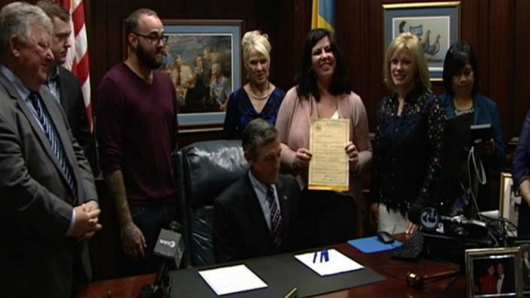 Kim DiSalvo holds Lorenzo's law after it was signed by Gov. John Carney in his Wilmington office.(Dan Rosenthal/WHYY)