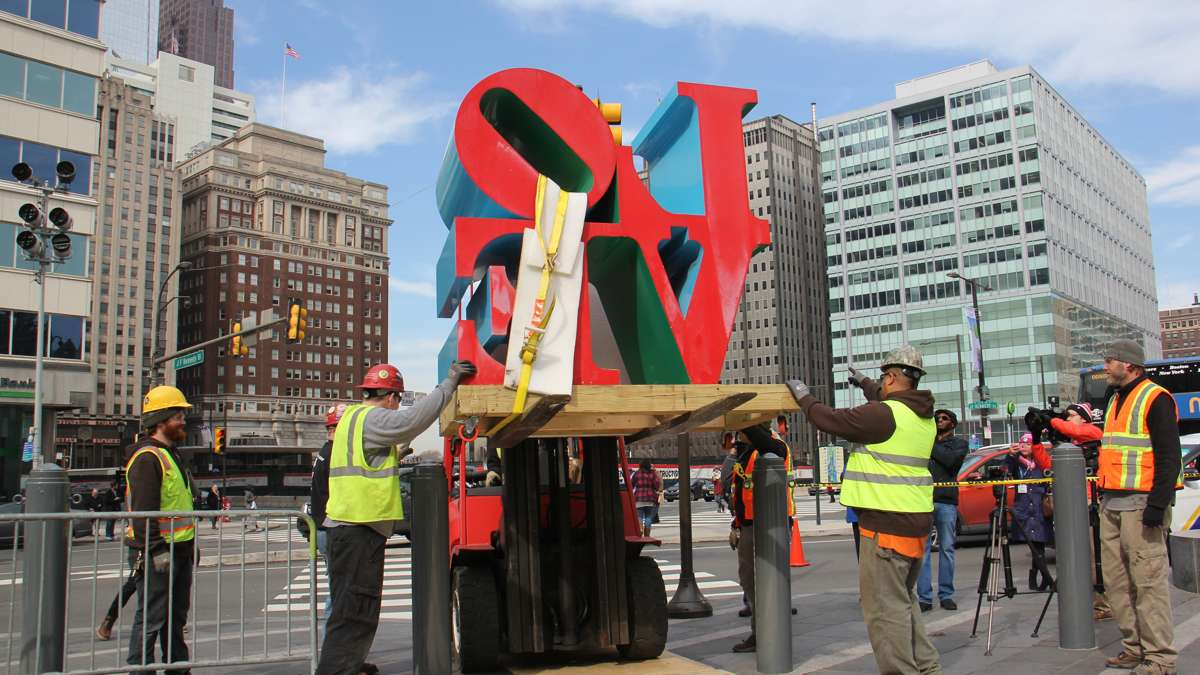 The sculpture is lifted over the barriers that protect Dilworth Park.
