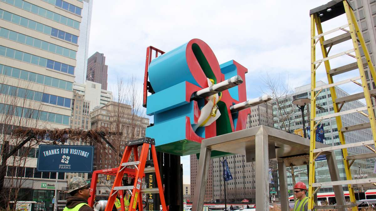 A forklift removes the top half of the LOVE sculpture.