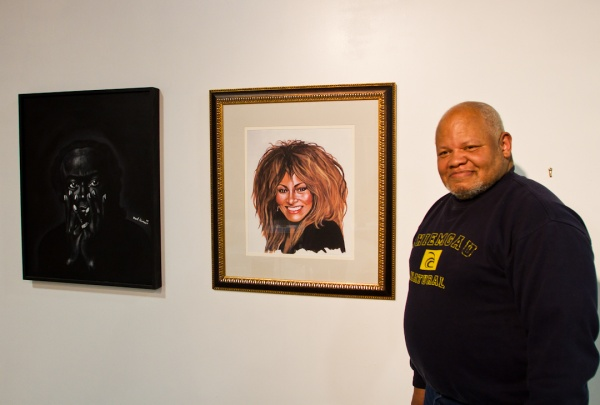 """<p><p>Karl Hanson stands next to his portraits, one of Miles Davis (right) and the other of Tina Turner. He says he saw both as photographs in magazines and that, """"they just said, paint me.""""(Brad Larrison/for NewsWorks)</p></p>"""