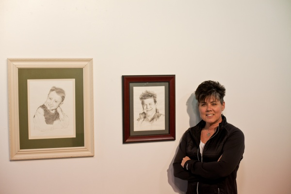 "<p><p>Loraine Dunn, art director for Mt. Airy Art Garage, standing next to her drawings, ""Young Jerry"" (left) and ""Kathryn."" (Brad Larrison/for NewsWorks)</p></p>"
