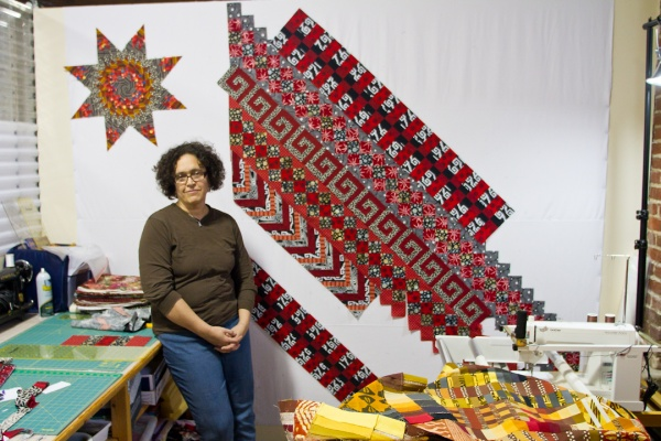 <p><p>Sarah Bond stands in the studio where she makes quilts in the Mt. Airy Art Garage. Bond has been quilting for 30 years and says it runs in the family. (Brad Larrison/for NewsWorks)</p></p>