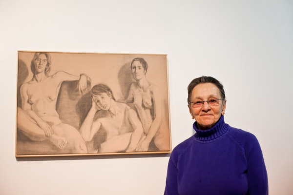 """<p><p>Arlene Olshan stands next to a portrait of herself, her best friend and her partner from when they were in art school. Olshan titled it """"Monumental.""""(Brad Larrison/for NewsWorks)</p></p>"""