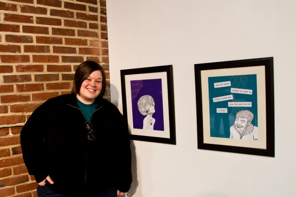 """<p><p>Melissa Hamilton stands next to her literature-influenced cartoons, """"Secrets of Living"""" (right), and """"The World Was a Symphony."""" Hamilton is an English teacher by day but has been cartooning since she was a child.(Brad Larrison/for NewsWorks)</p></p>"""