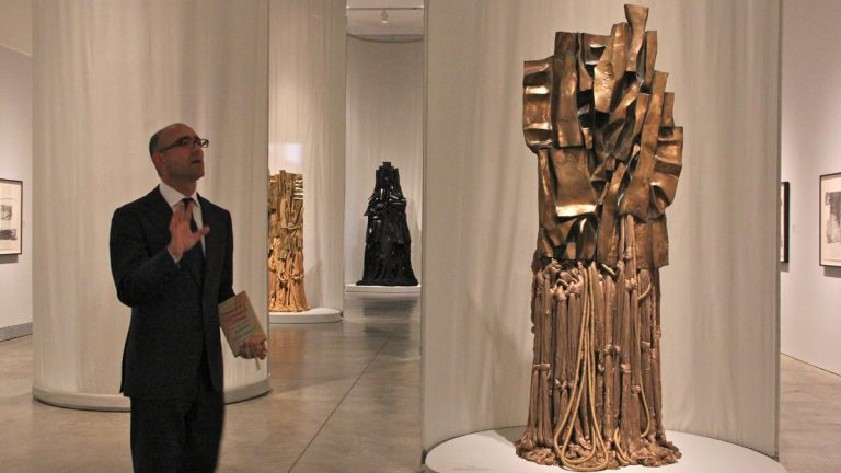 Carlos Bosualdo, curator of contemporary art at the Philadelphia Museum of Art, leads visitors through The Malcolm X Steles by Barbara Chase-Riboud. (Emma Lee/for NewsWorks)
