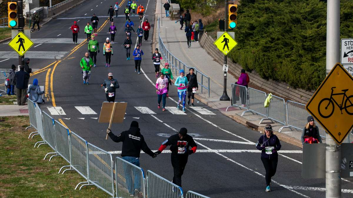 A runner gets a high five as he enters the final leg of the course during the Philadelphia Marathon.