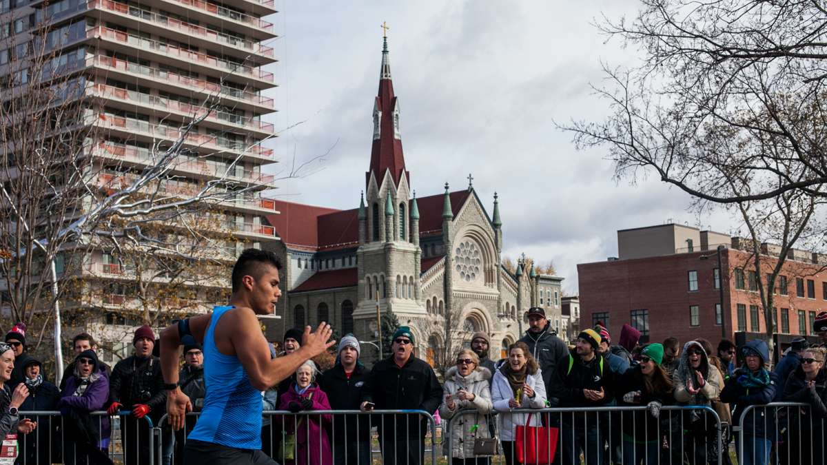 Spectators cheer as runners approach the finish line of the Philadelphia Marathon.
