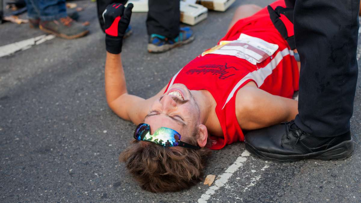 A runner collapses after crossing the finish line during the Philadelphia Marathon.